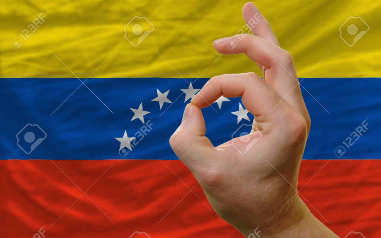 man showing excellence or ok gesture in front of complete wavy venezuela national flag of  symbolizing best quality, positivity and succes Stock Photo - 14428758