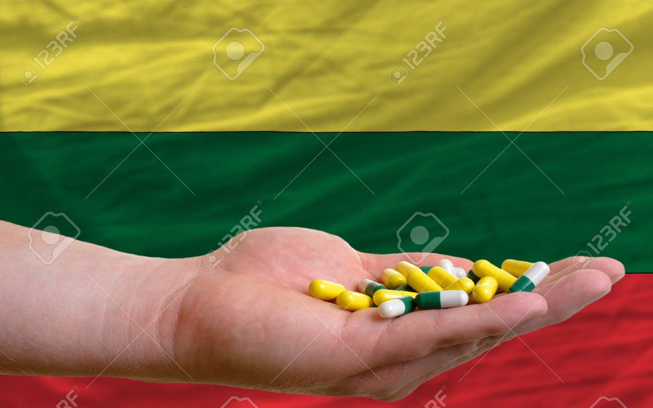 man holding capsules in front of complete wavy national flag of lithuania symbolizing health, medicine, cure, vitamines and healthy life Stock Photo - 14428453