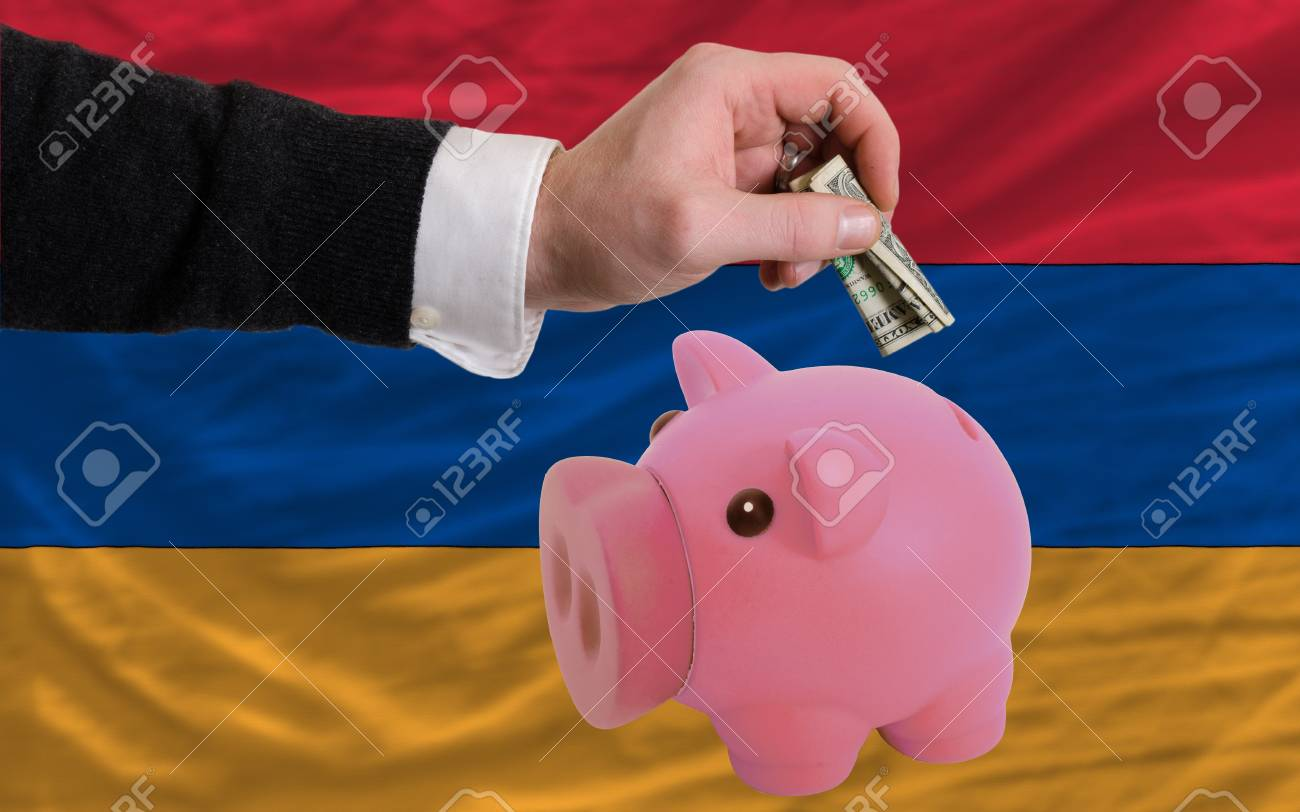 Man putting dollar into piggy rich bank national flag of armenia in foreign currency because of inflation Stock Photo - 17921764