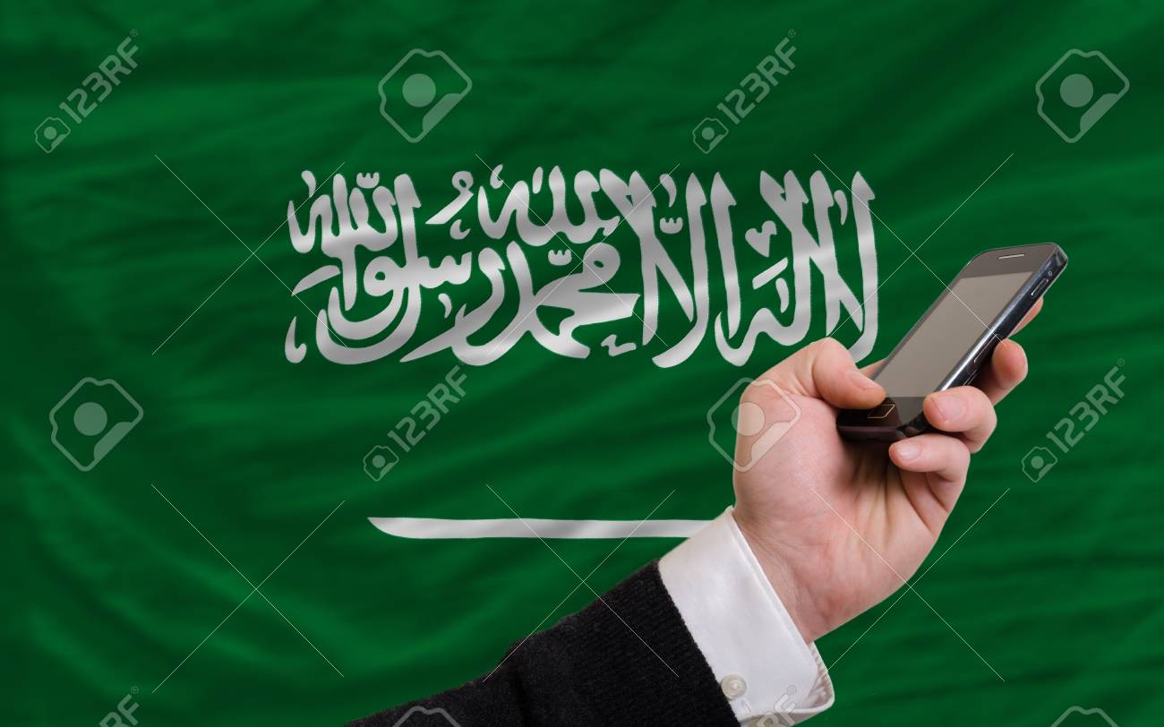 man holding cell phone in front national flag of saudi arabia