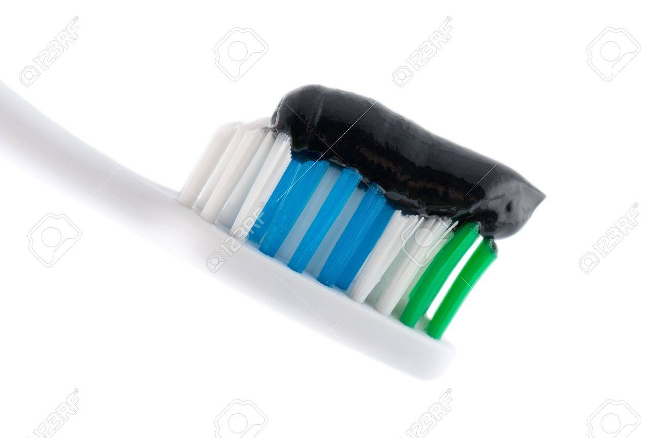 A toothbrush with black toothpaste over white in a dental hygiene and tooth care concept Stock Photo - 12682341