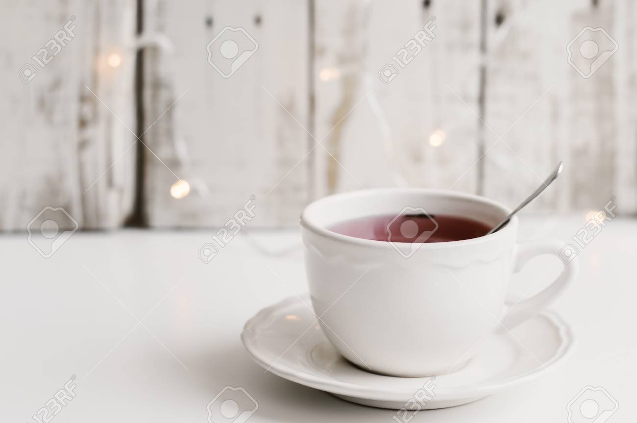 Red Tea In A Small White Cup On White Table Wood And Small Yellow