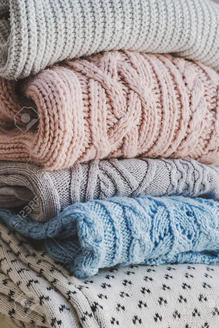 Pile of knitted woolen sweaters. Warm clothes for fall and winter season. Knitwear storage and care - 155867761