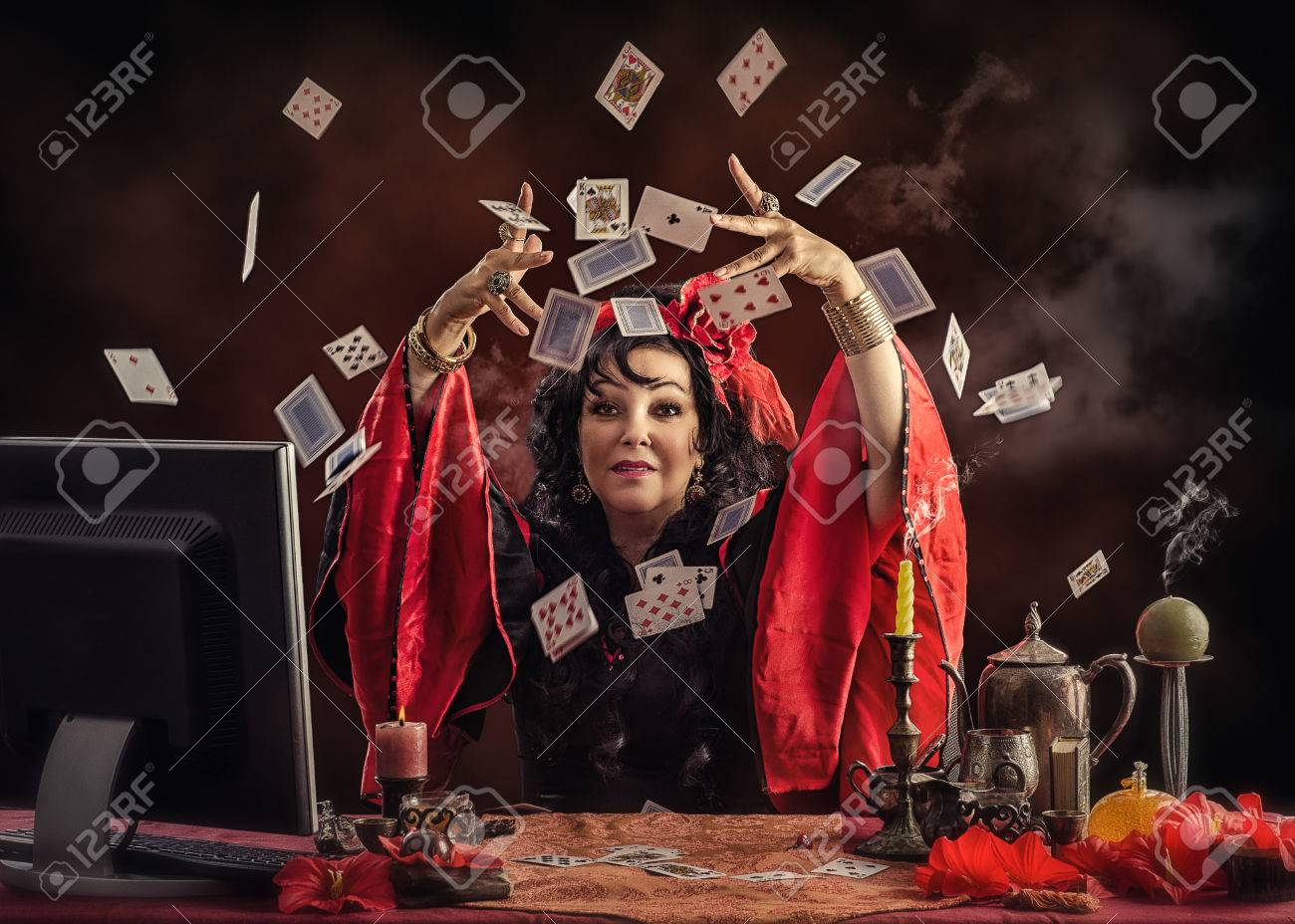 Mature Gypsy fortune-teller sitting opposite monitor tossing