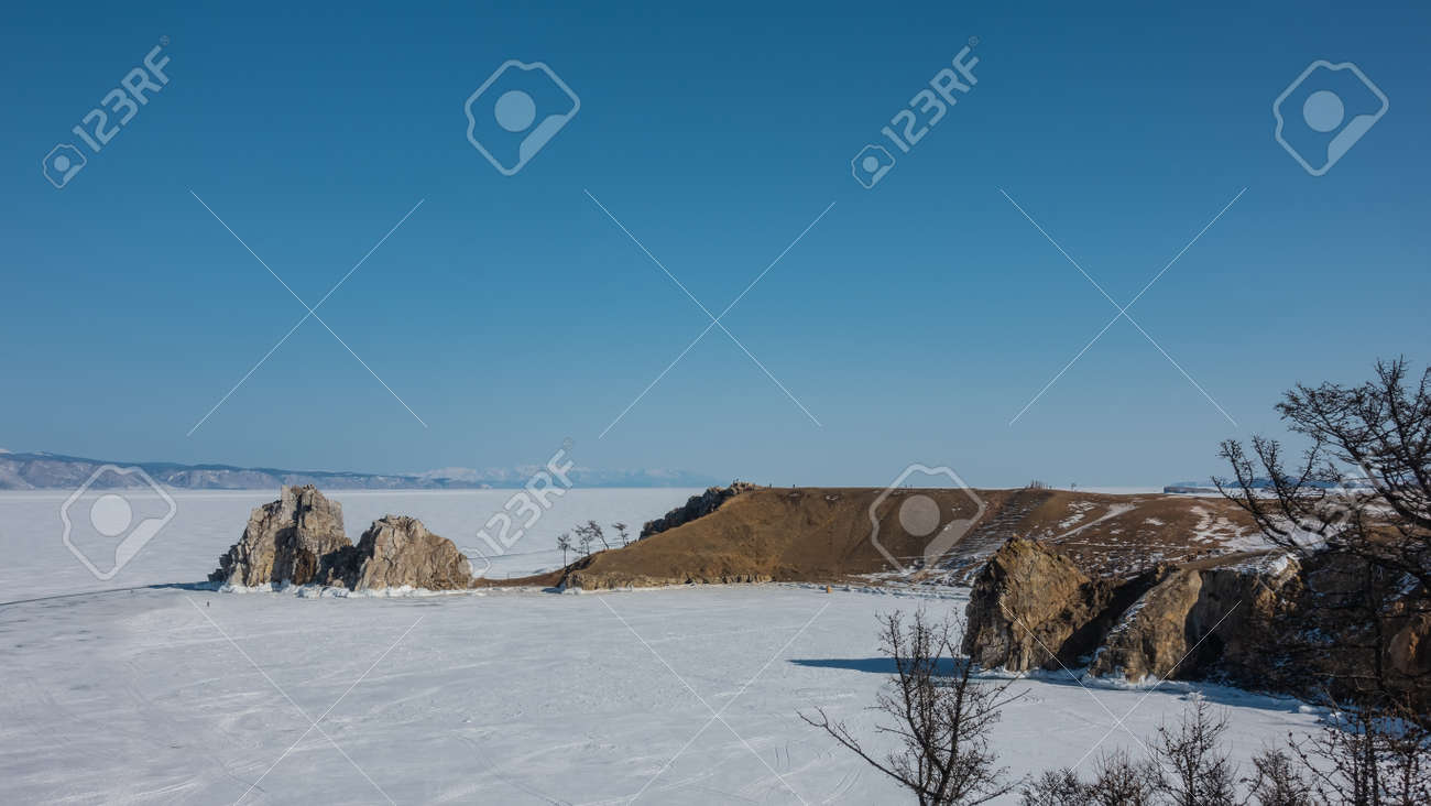 In the vastness of the frozen lake, an unusual two-headed rock, devoid of vegetation, rises. Steep rocky slopes. The ice is completely covered with snow. Clear blue sky. Baikal - 169016937