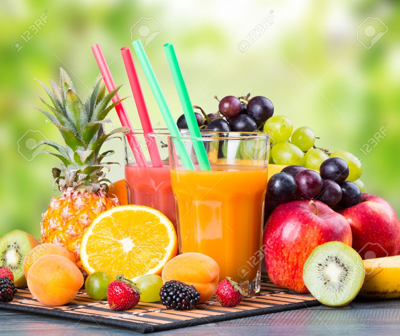Fresh juice with fruits on wooden table with nature green background - 44154183
