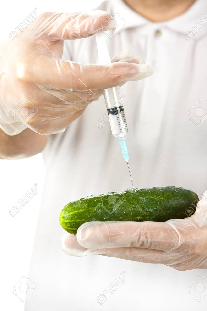 Hands in disposable gloves injecting cucumber with syringe over white background Stock Photo - 14409282