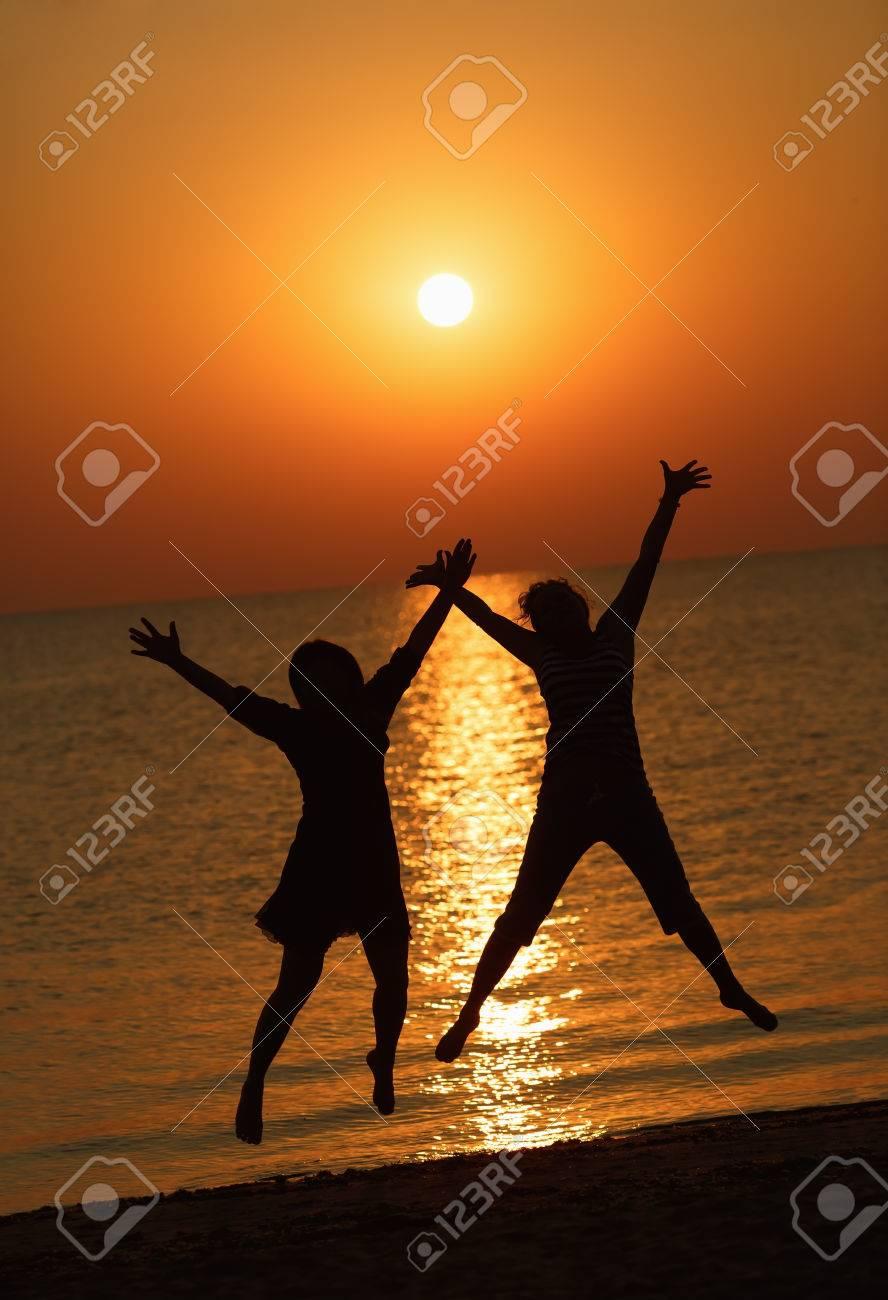 Due Ragazze Che Salta Su Uno Sfondo Del Sole Che Sorge Sul Mare Concentrarsi Su Modelli Profondità Di Campo Tonica Immagine