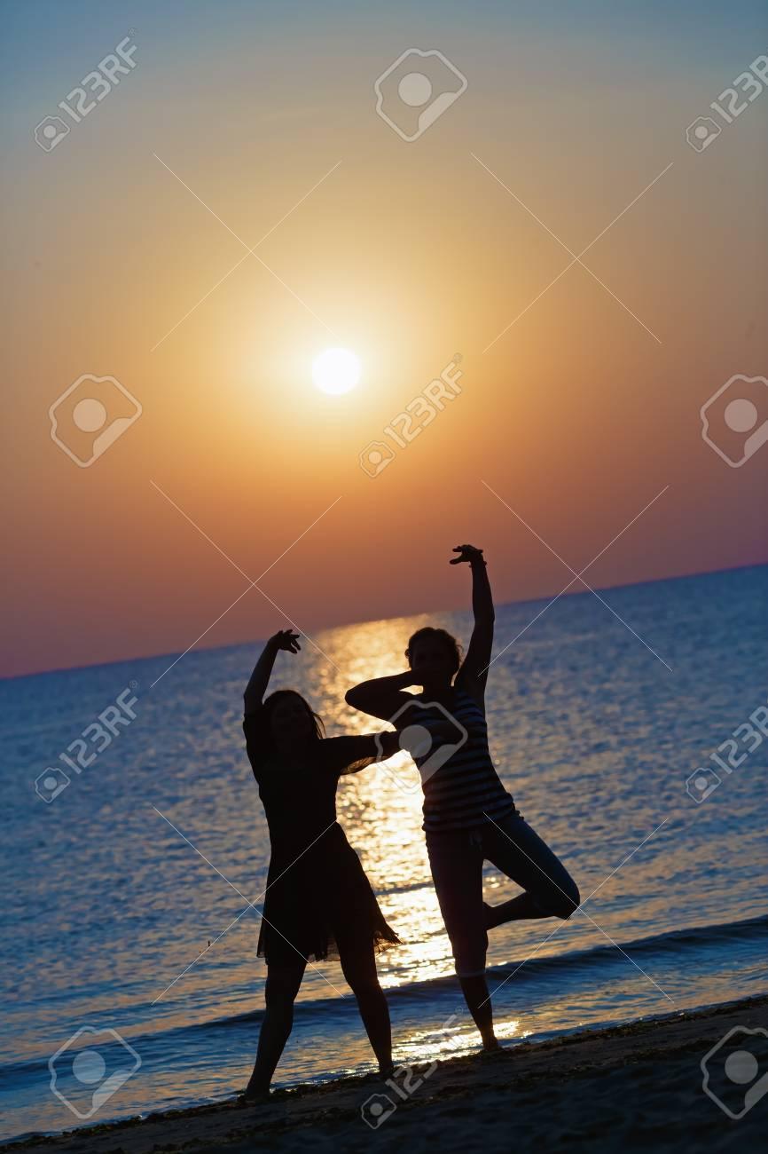 Due Ragazze Che Ballano Al Tramonto Su Uno Sfondo Di Mare Concentrarsi Su Modelli Profondità Di Campo Tonica Immagine