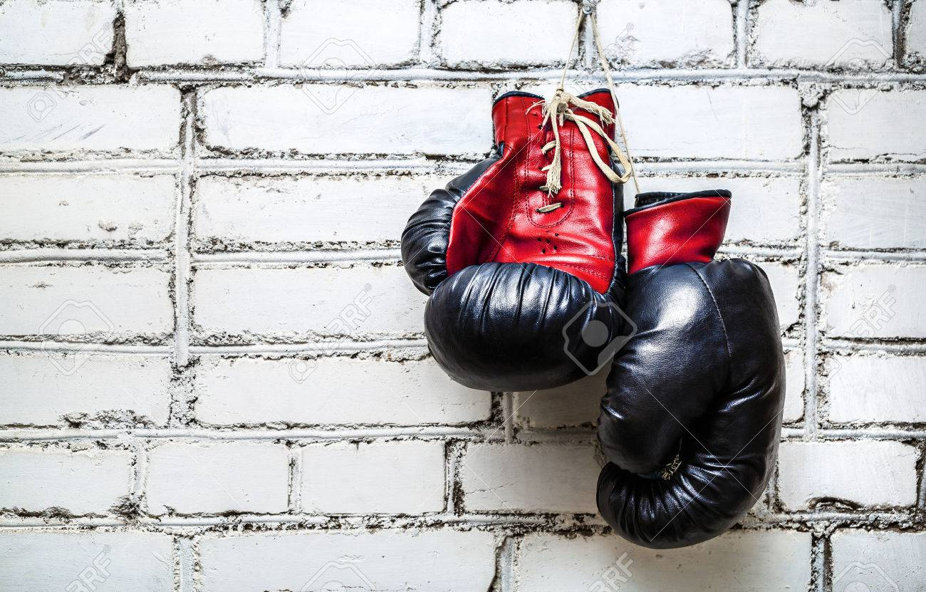 Pair of old red and black boxing gloves hanging on white brick wall. - 52132528