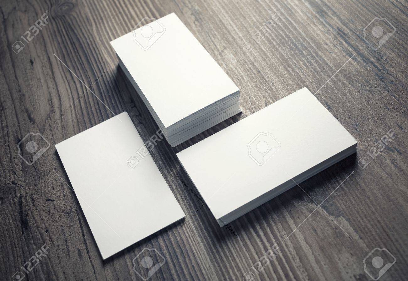 three piles of blank business cards on wood table background