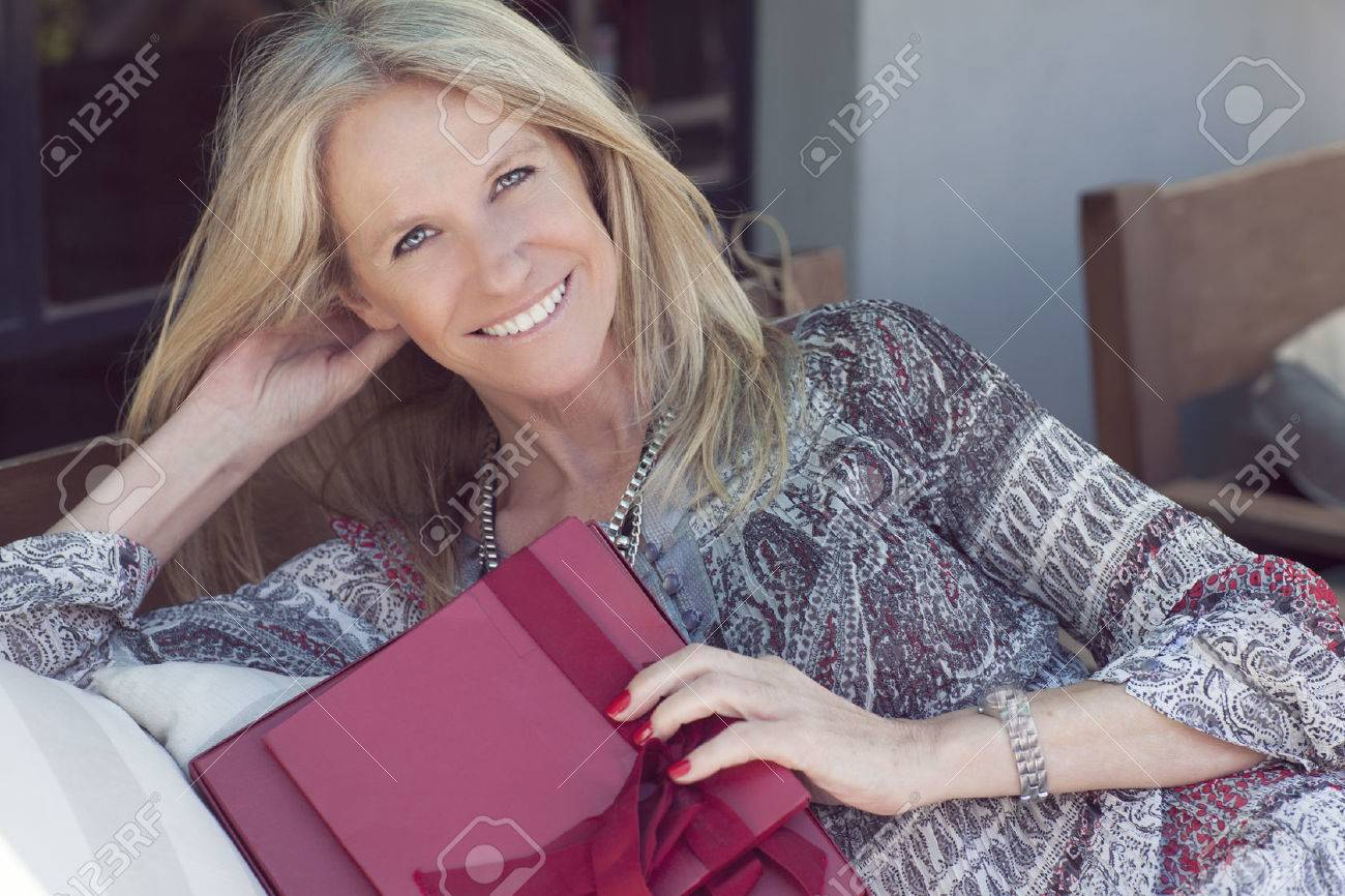 Happy Cute middle age woman with gift in outdoors - 52417867