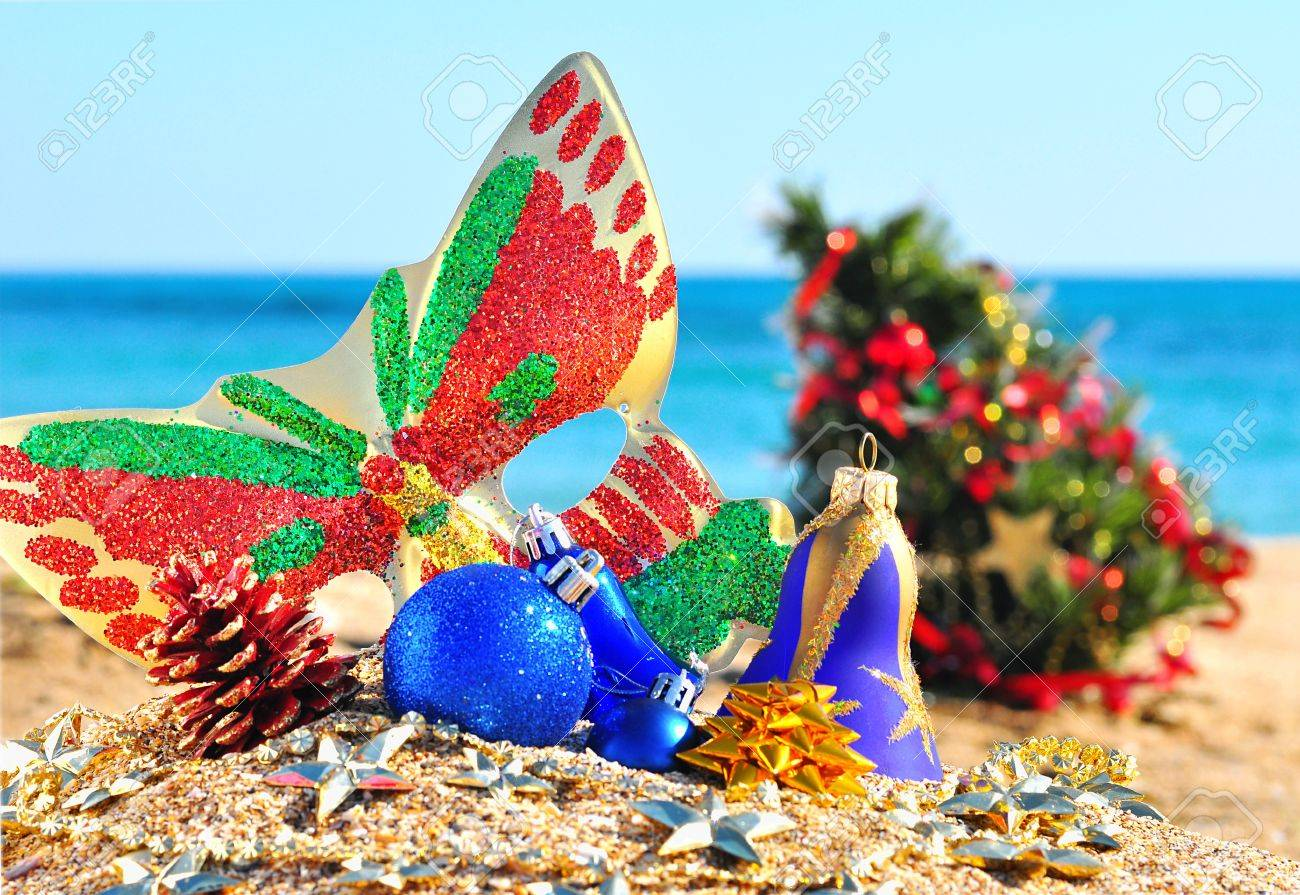 Christmas baubles, face mask, christmas tree on the sand in the beach Stock Photo - 16019420