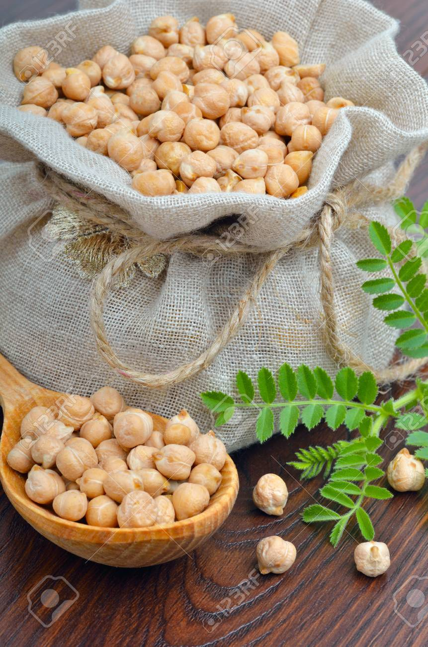 Chickpeas in a burlap bag on a wooden background - 39604235