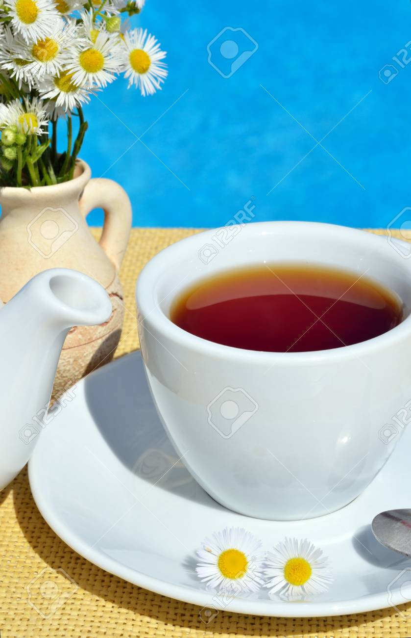 Black tea in a cup in front of the pool. - 60206318