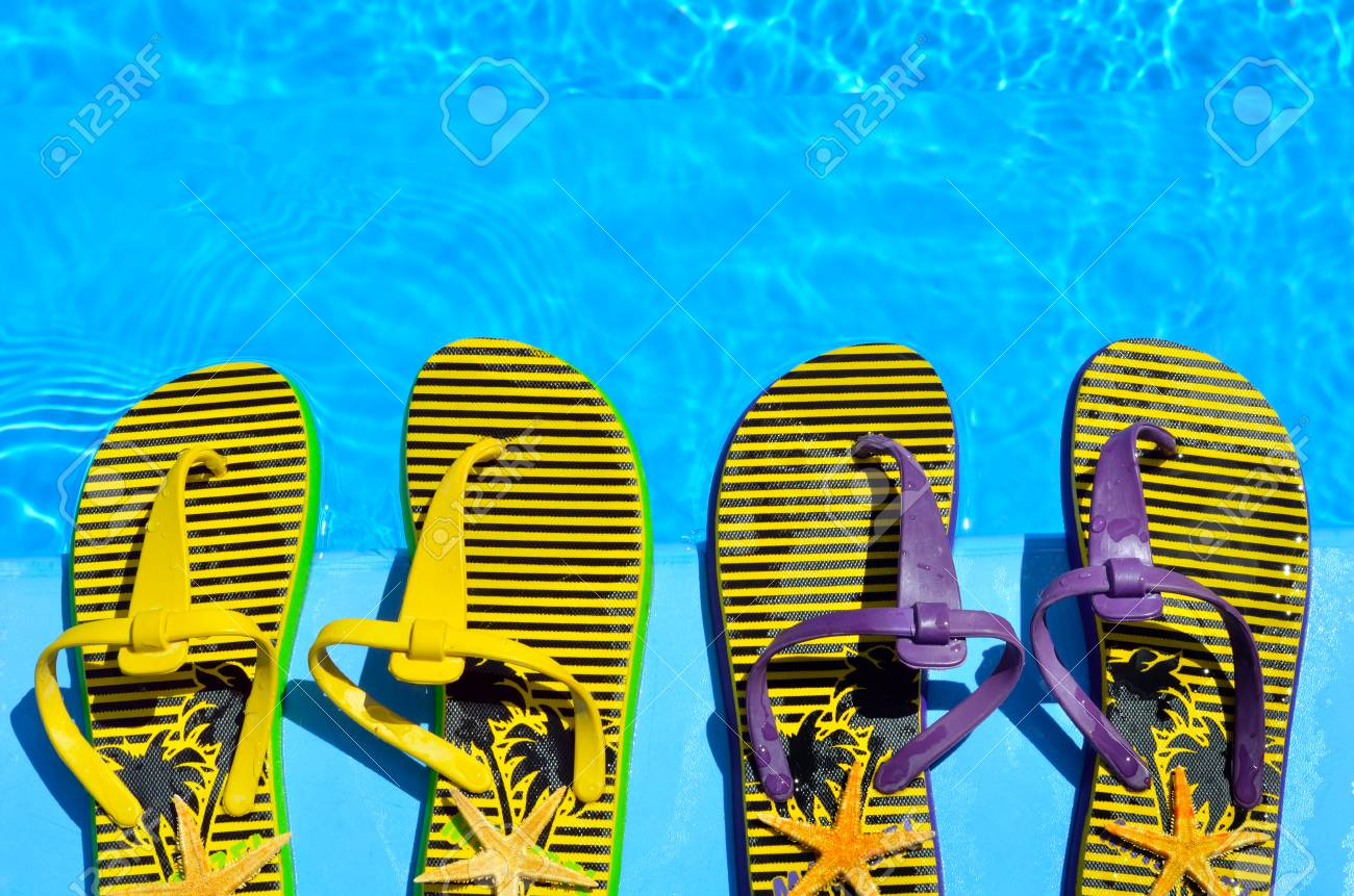 Flip-flops and starfish in the pool background. - 60206317