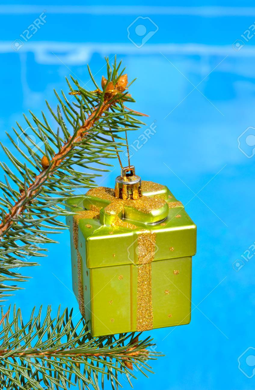 Christmas decoration on a branch of spruce opposite the pool. - 60807689
