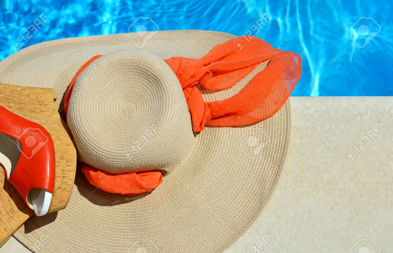 Woman beach hat and red sandals on the pool background. - 60807704
