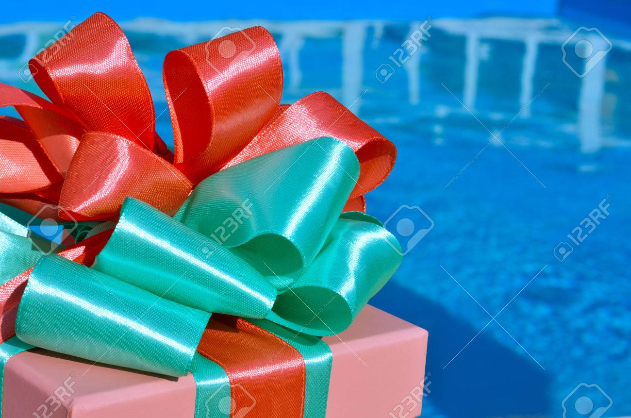 Gift box against the background of the blue pool. - 60807705