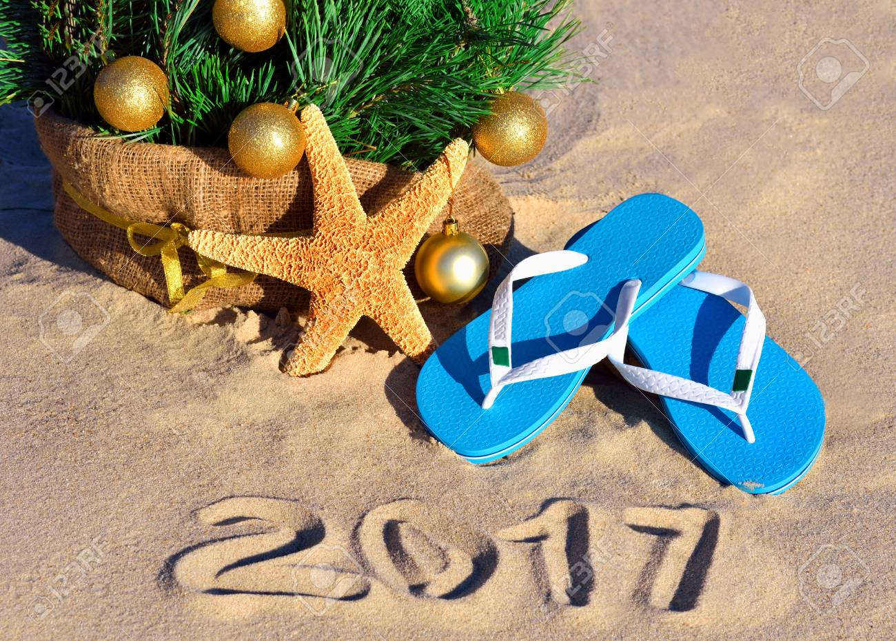 Christmas tree with christmas balls, slippers and starfish on the sand on beach - 67643971