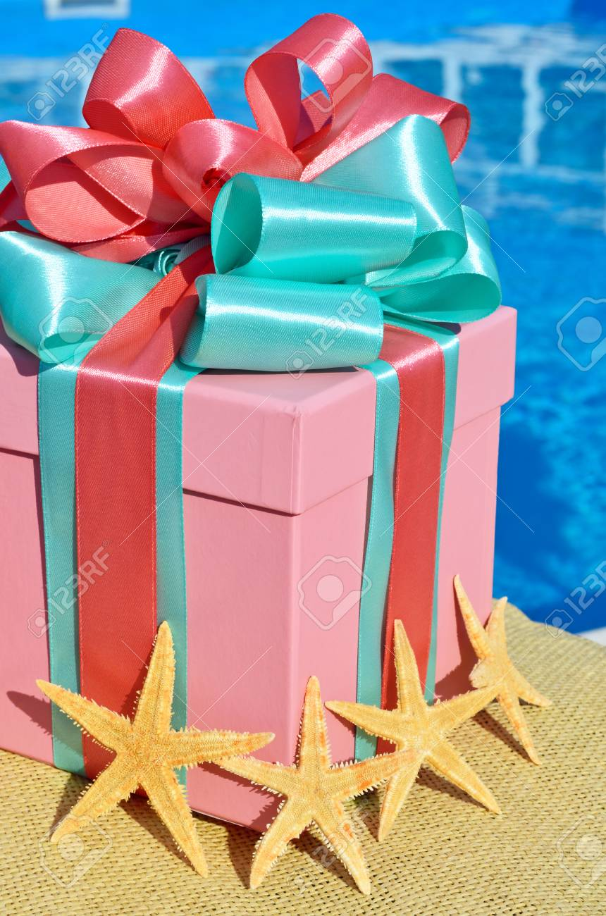 Gift box against with starfish the background of the blue pool. - 68713420