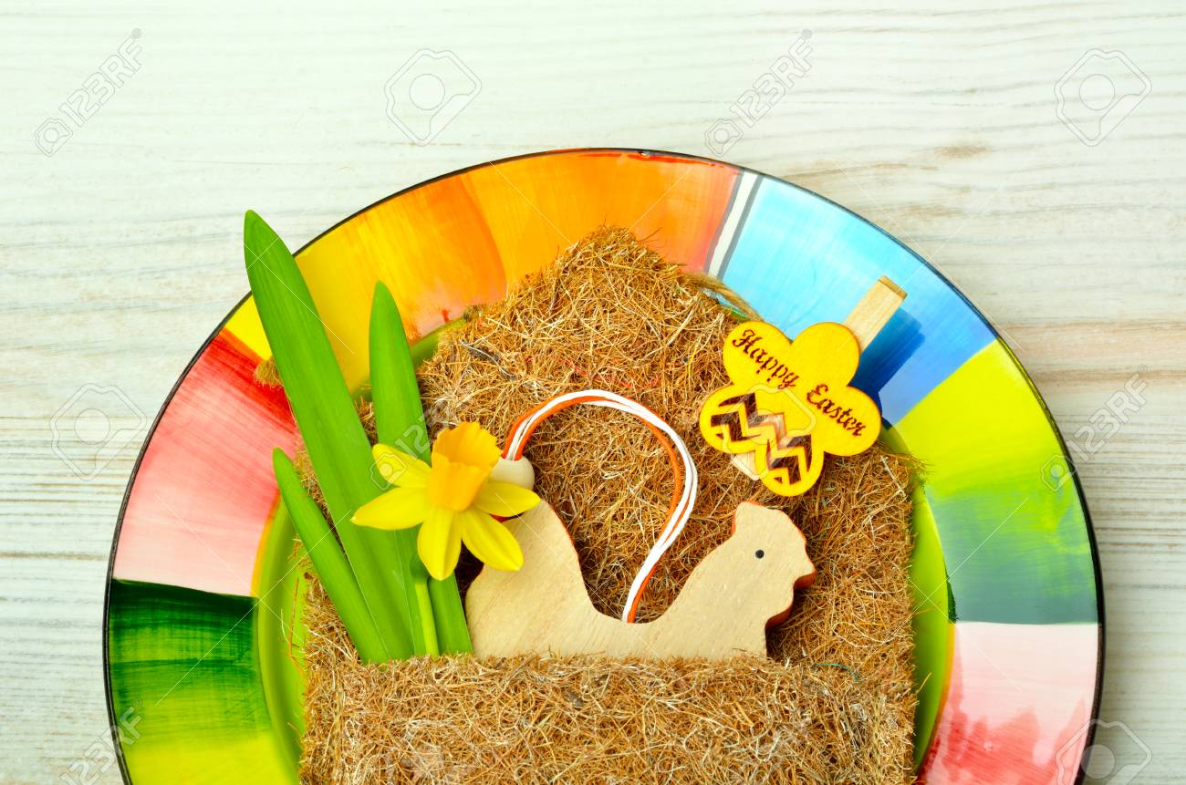 Easter decoration and fresh spring narcissus flowers on colored plate. - 71998445