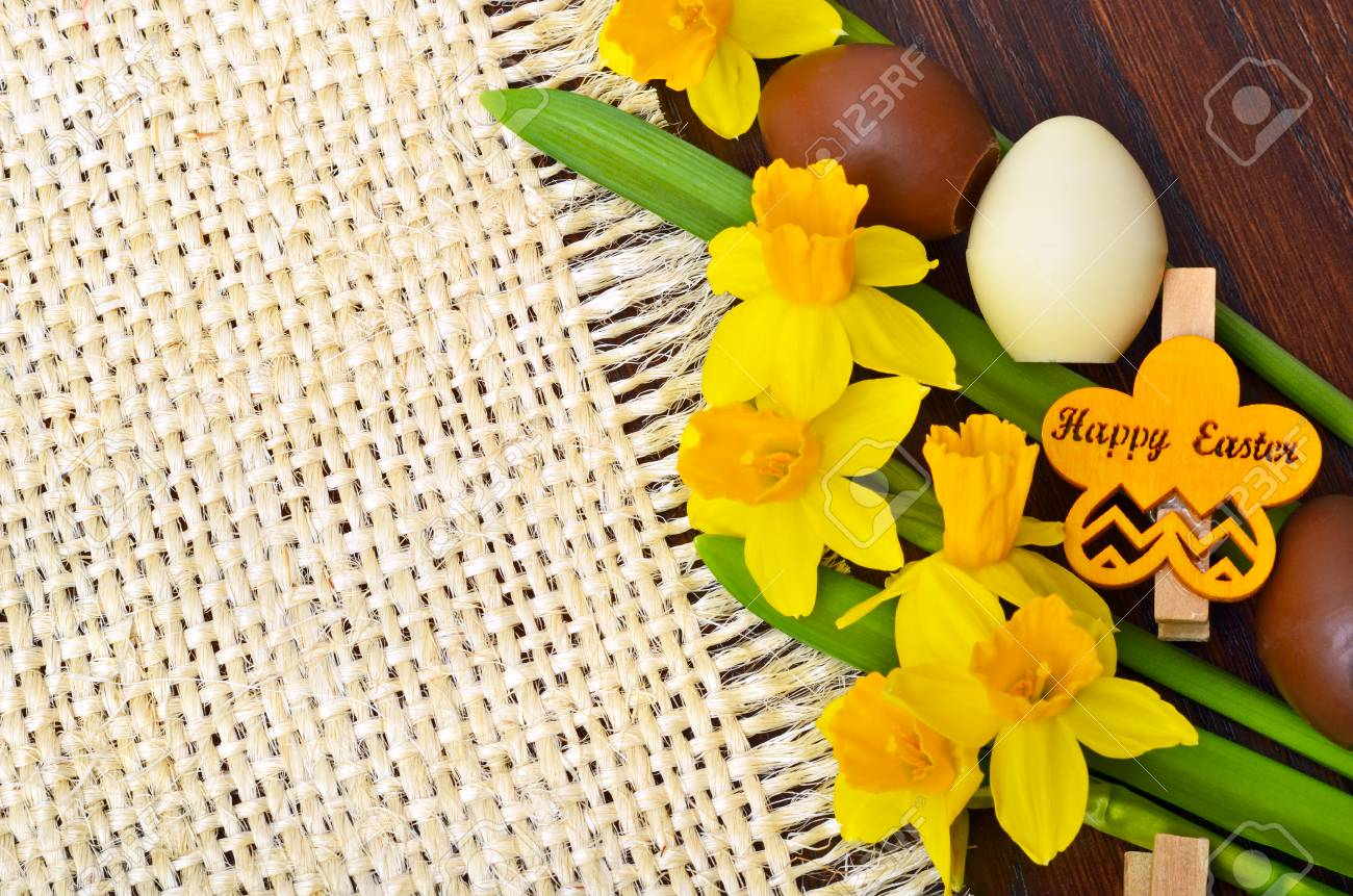 Easter decoration, fresh spring narcissus flowers and chocolate eggs. - 72039207