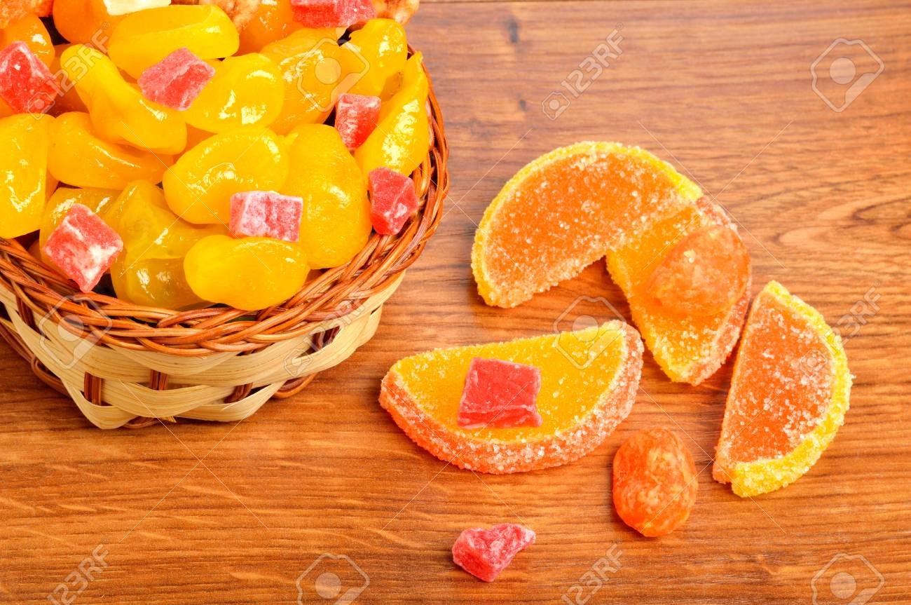 colorful candies and jellies in basket on wooden background - 71998276