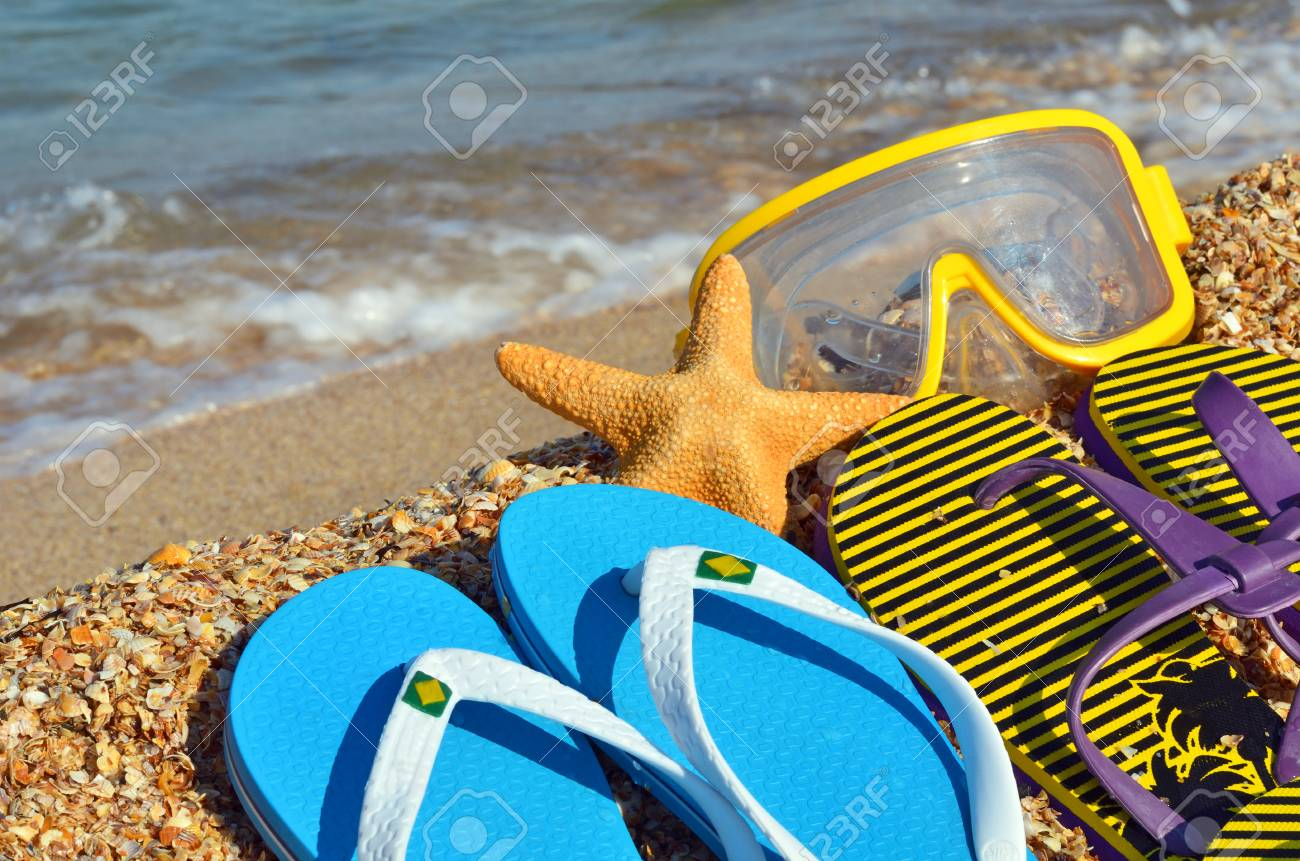Colorful flip flops, starfish and underwater mask on the beach. - 72044722