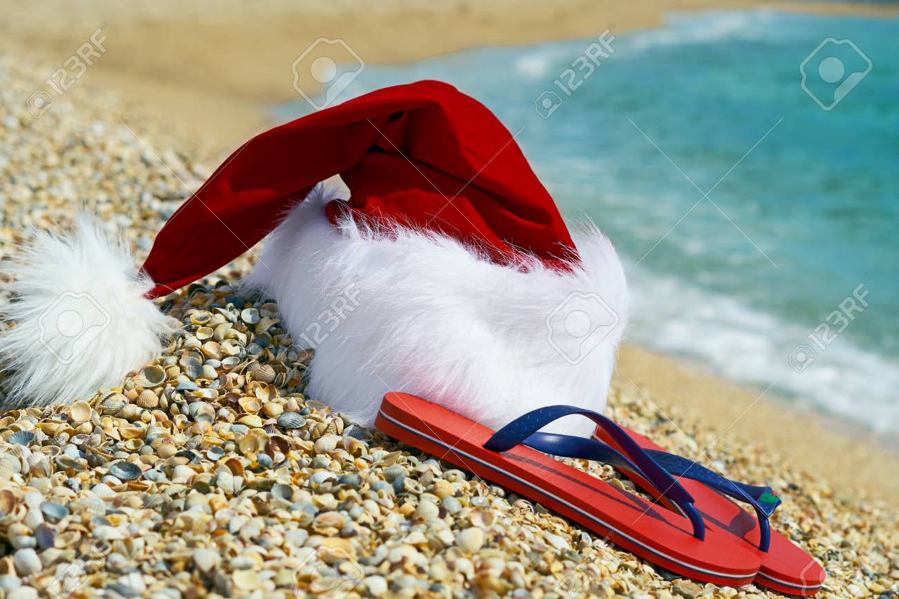 Santa Claus hat and flip flops оn sand on the sea background. - 89507860