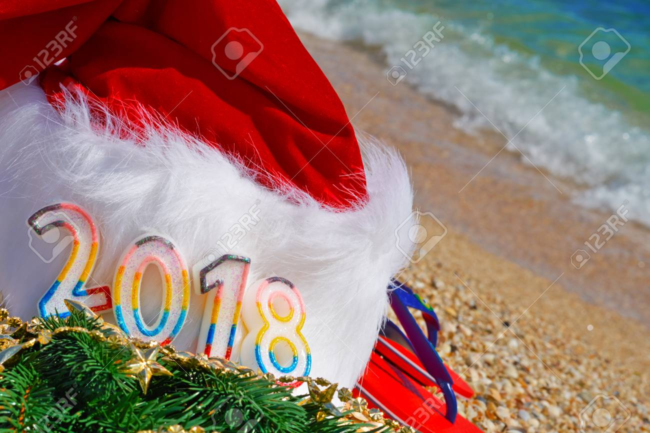 Santa Claus hat and toys оn sand on the sea background. 2018 - 90585943