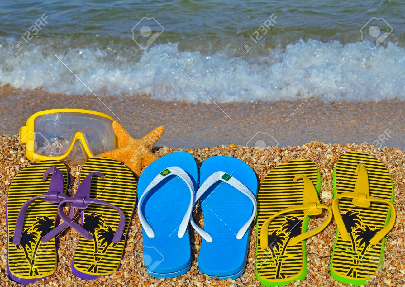 Colorful flip flops, starfish and underwater mask on the beach. - 90677729