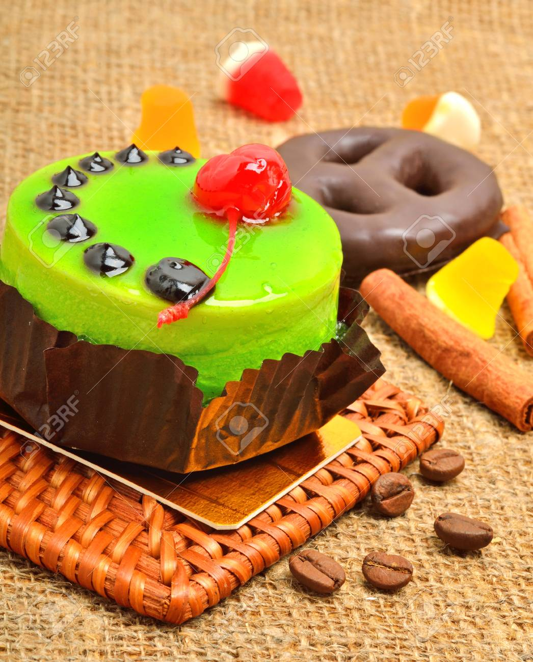 Cake in green jelly with cherry and chocolate icing on sackcloth. - 95052196