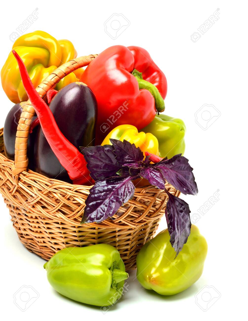 Sweet peppers, eggplant, chilli pepper and basil in the basket isolated on white background - 121736317