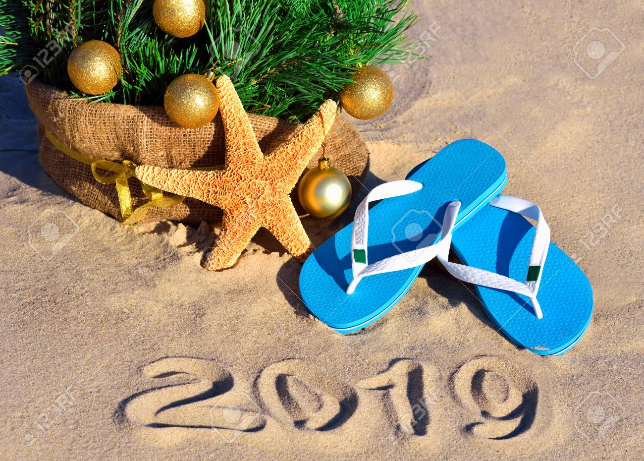 New Year 2019 on the beach. Christmas tree, starfish and slippers in sand - 121736319
