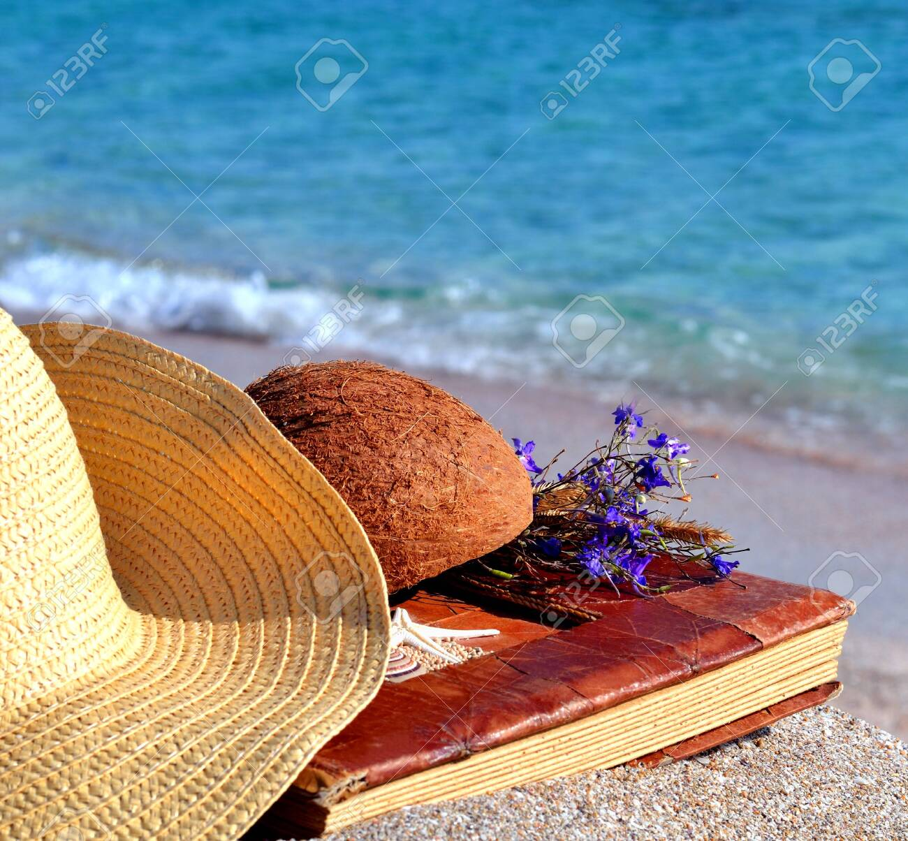 Vintage album with flower, hat and coconut on the seashore - 121736320