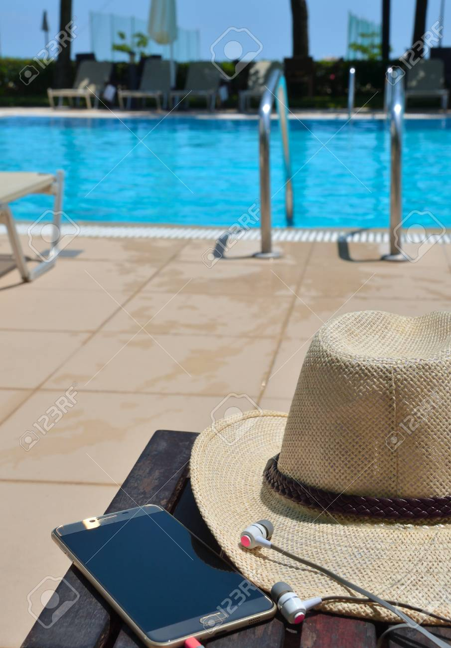 Hat with mobile phone and headphones on the green grass. Hotel in Greece. - 121735976