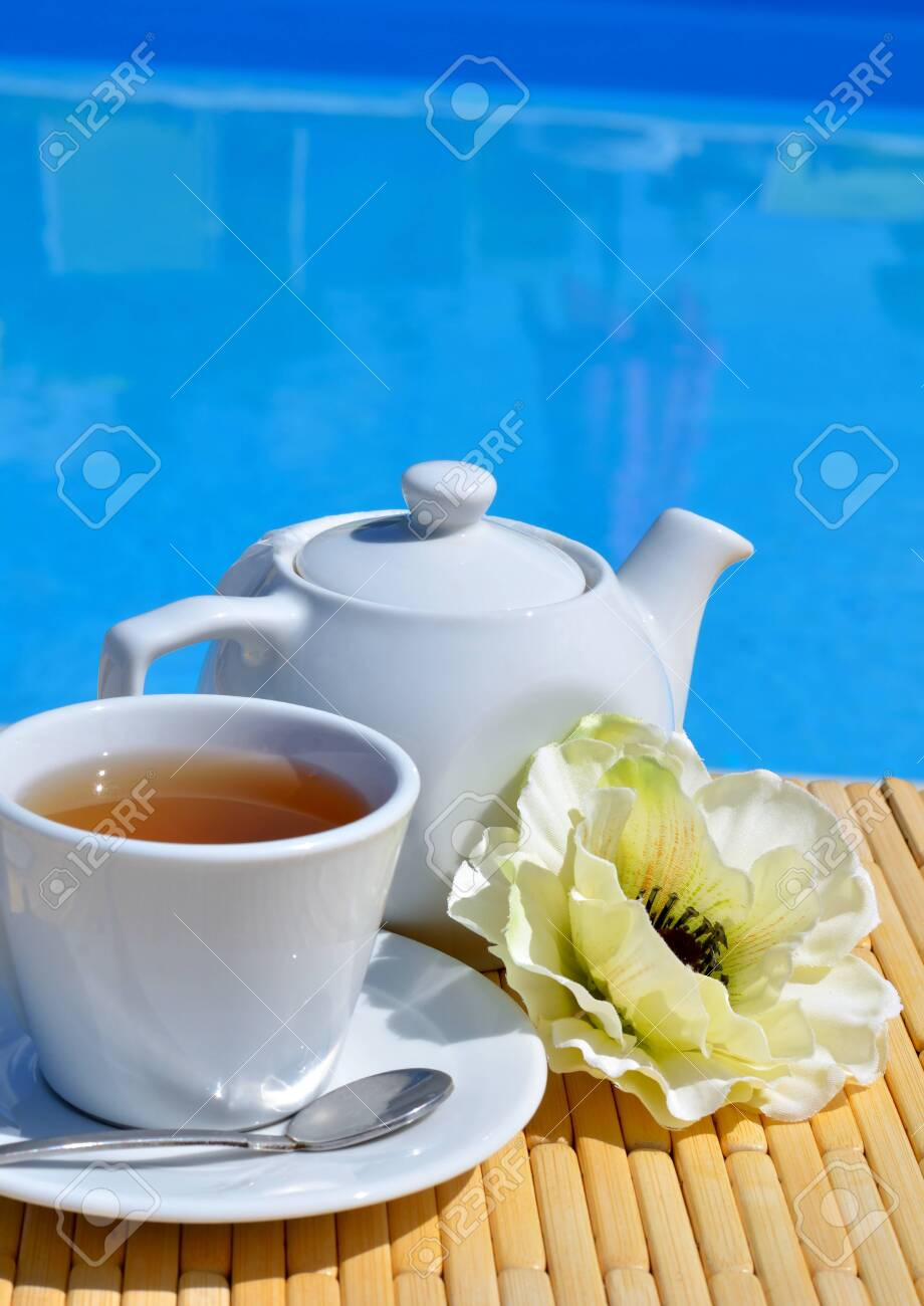 Tea in a cup with marmalade in front of the pool. - 121735981