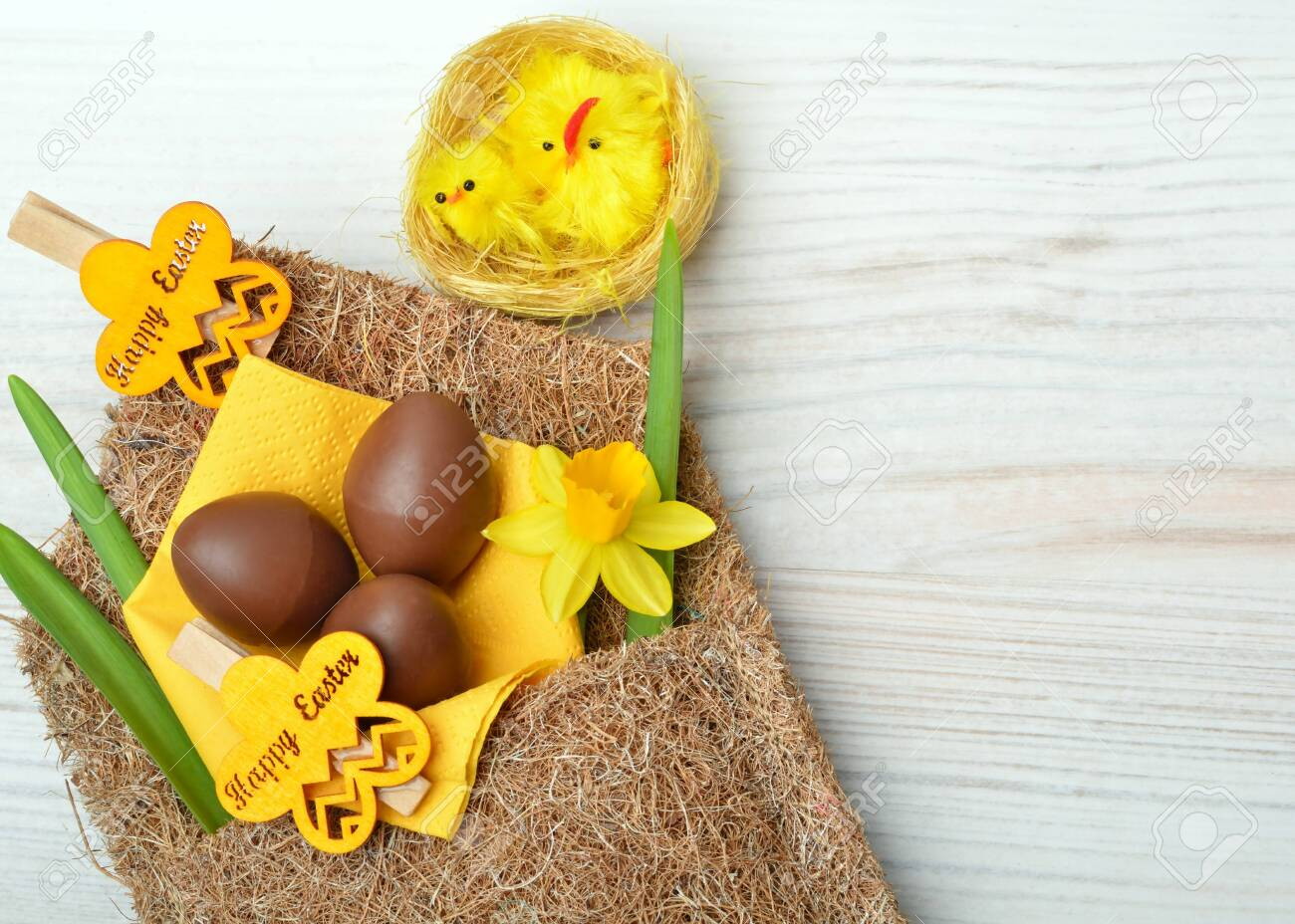 Easter decoration and fresh spring narcissus flowers on wooden background. - 121736040