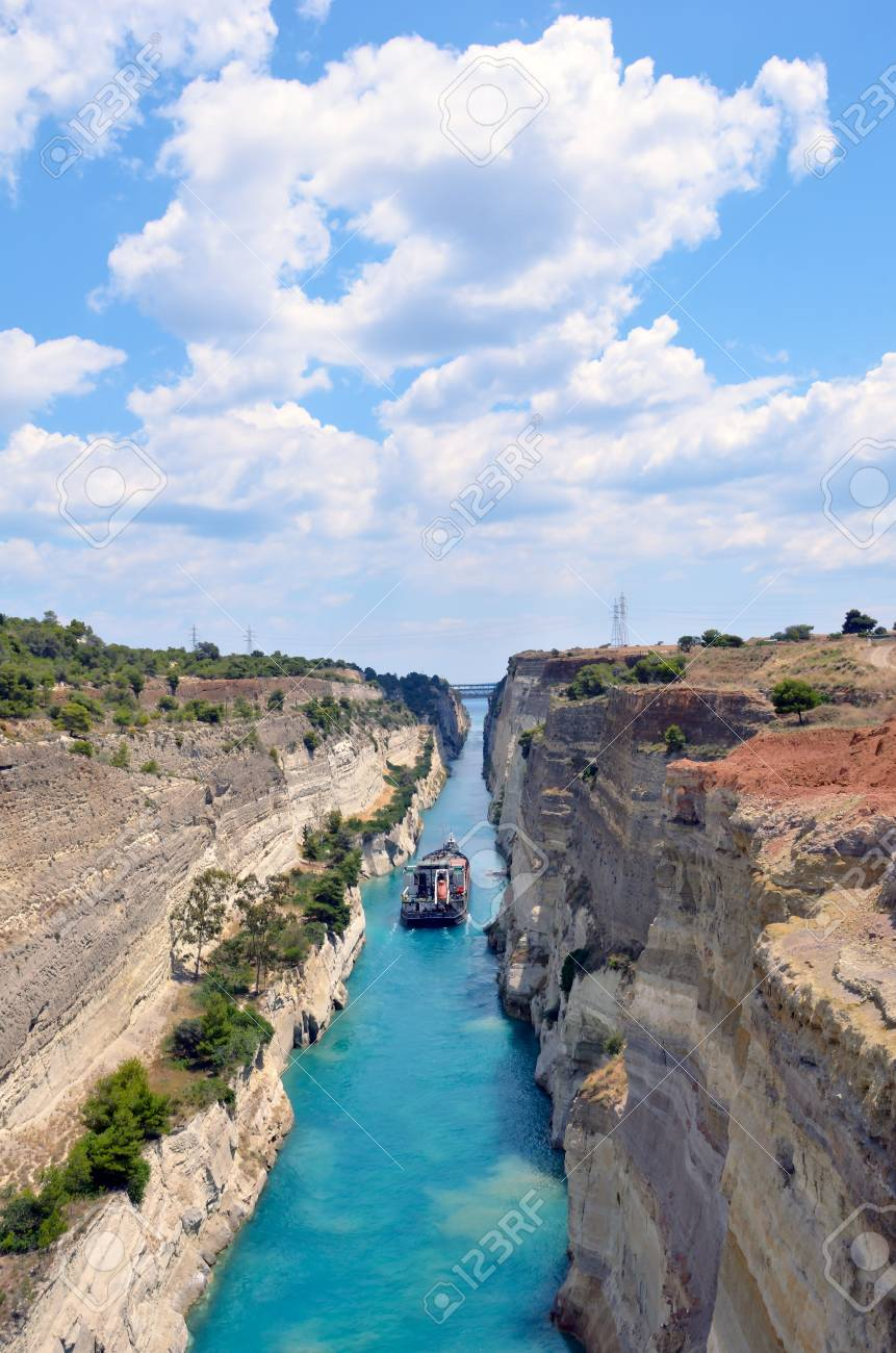 Corinth Canal in a bright sunny day against a blue sky. Among the rocks floating white yachts in turquoise water. - 121736059