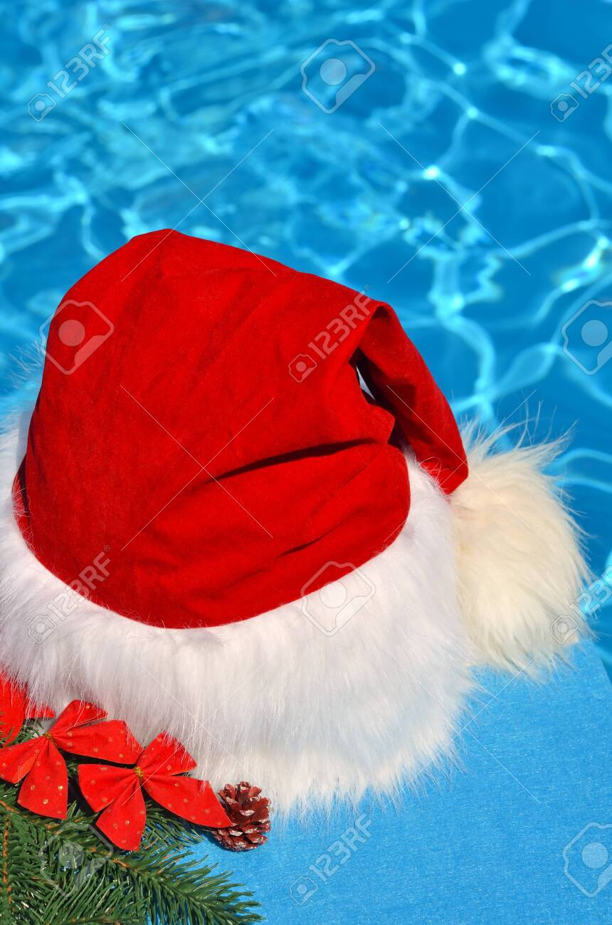 Santa Claus hat on a branch of spruce and toys opposite the pool. - 137887466