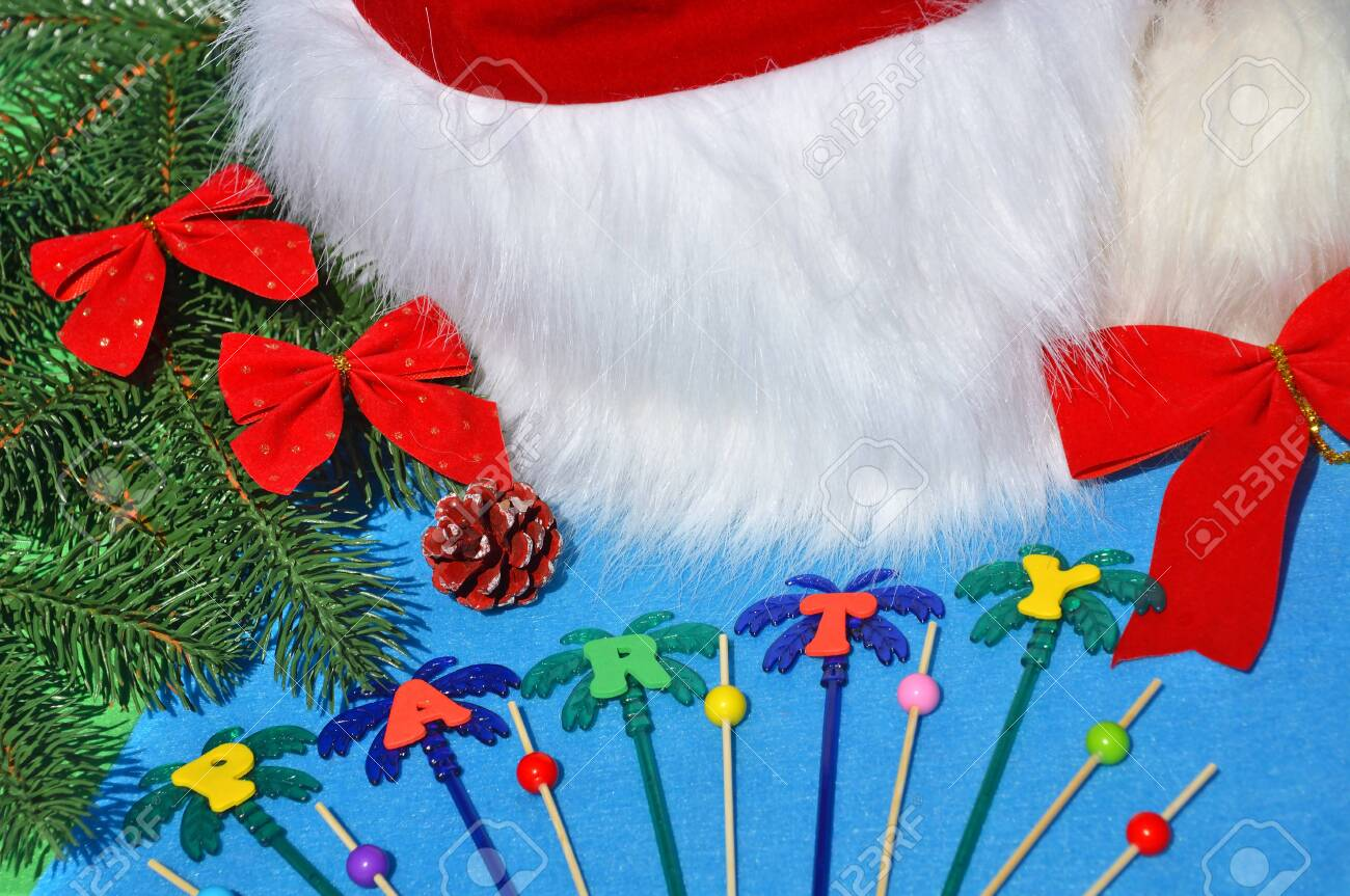 Santa Claus hat on a branch of spruce and toys opposite the pool. - 137887470