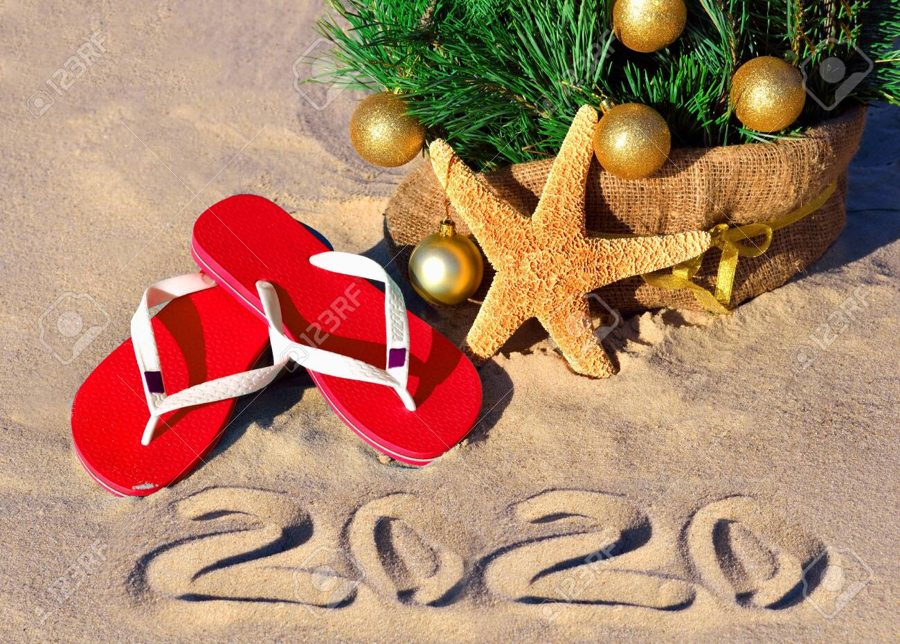 New Year 2020 on the beach. Christmas tree, starfish and slippers in sand - 137932582