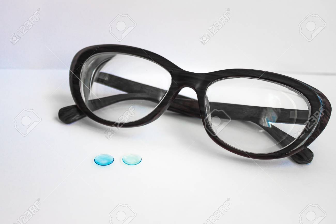 a5929d54bfc0 Female black rim for glasses, next to two contact lenses. White background,  daylight
