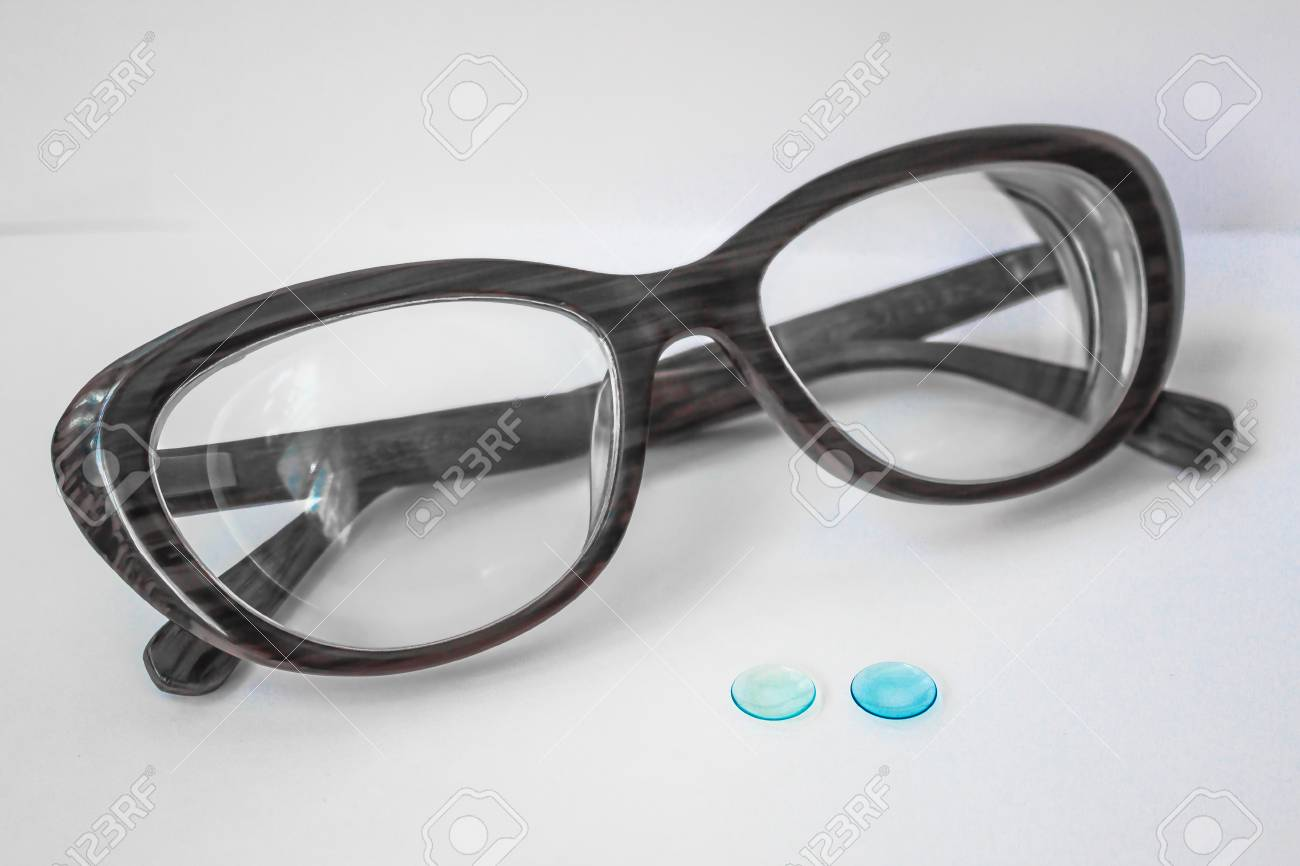27178744619 Stock Photo - Two small lenses for the eyes and thick female glasses. Myopia  of a high degree. Modern correction of vision. Rigid contact lenses are blue .