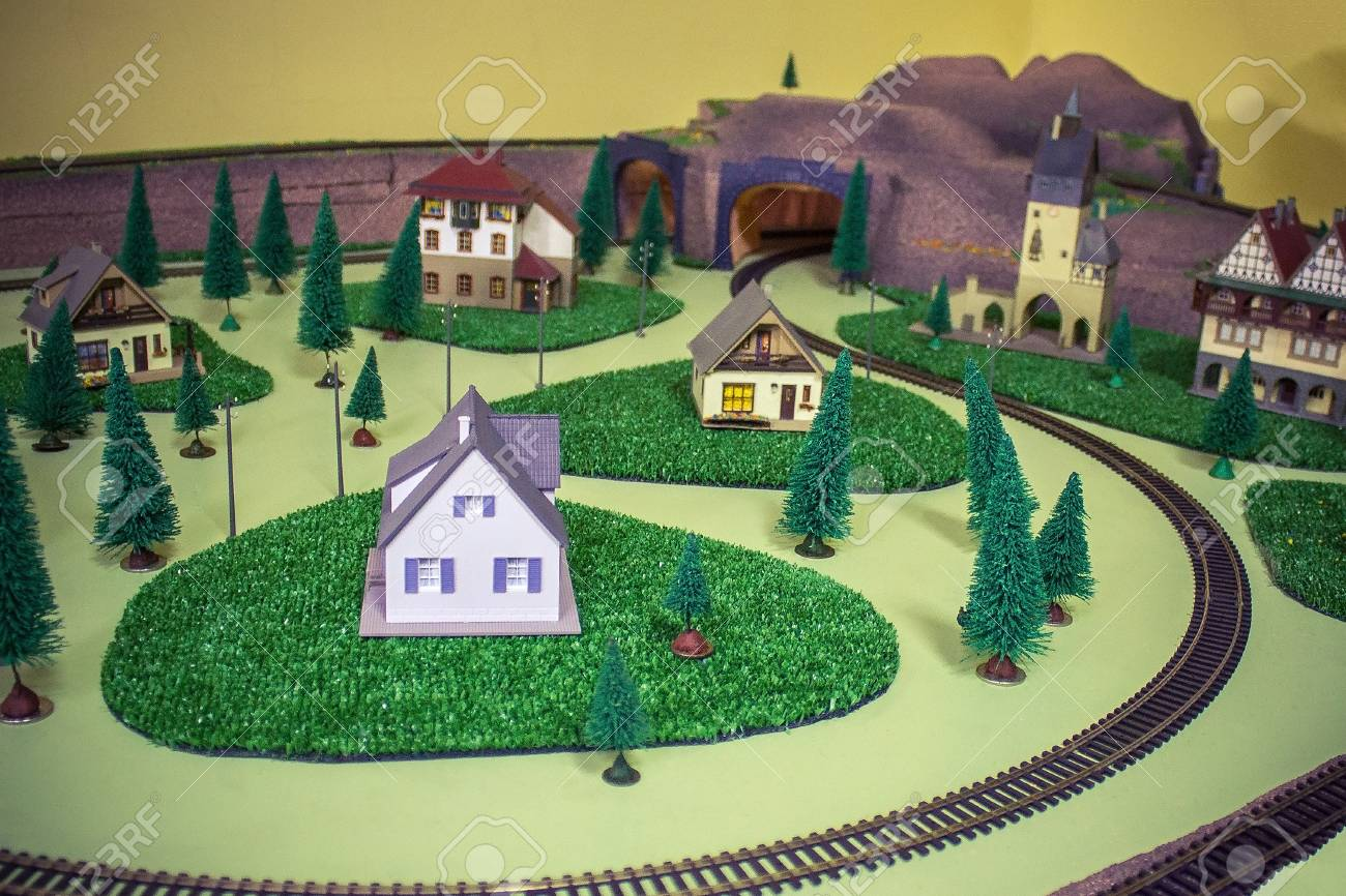 Toy buildings, railway, trees  Away the tunnel  A small town,