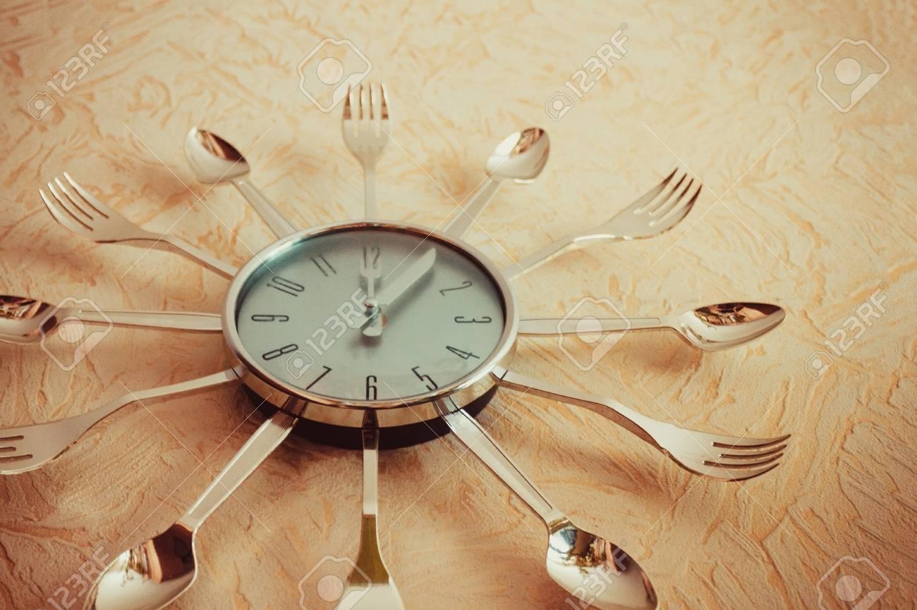 Modern kitchen clock made of metal, arrows indicate noon. Bon..