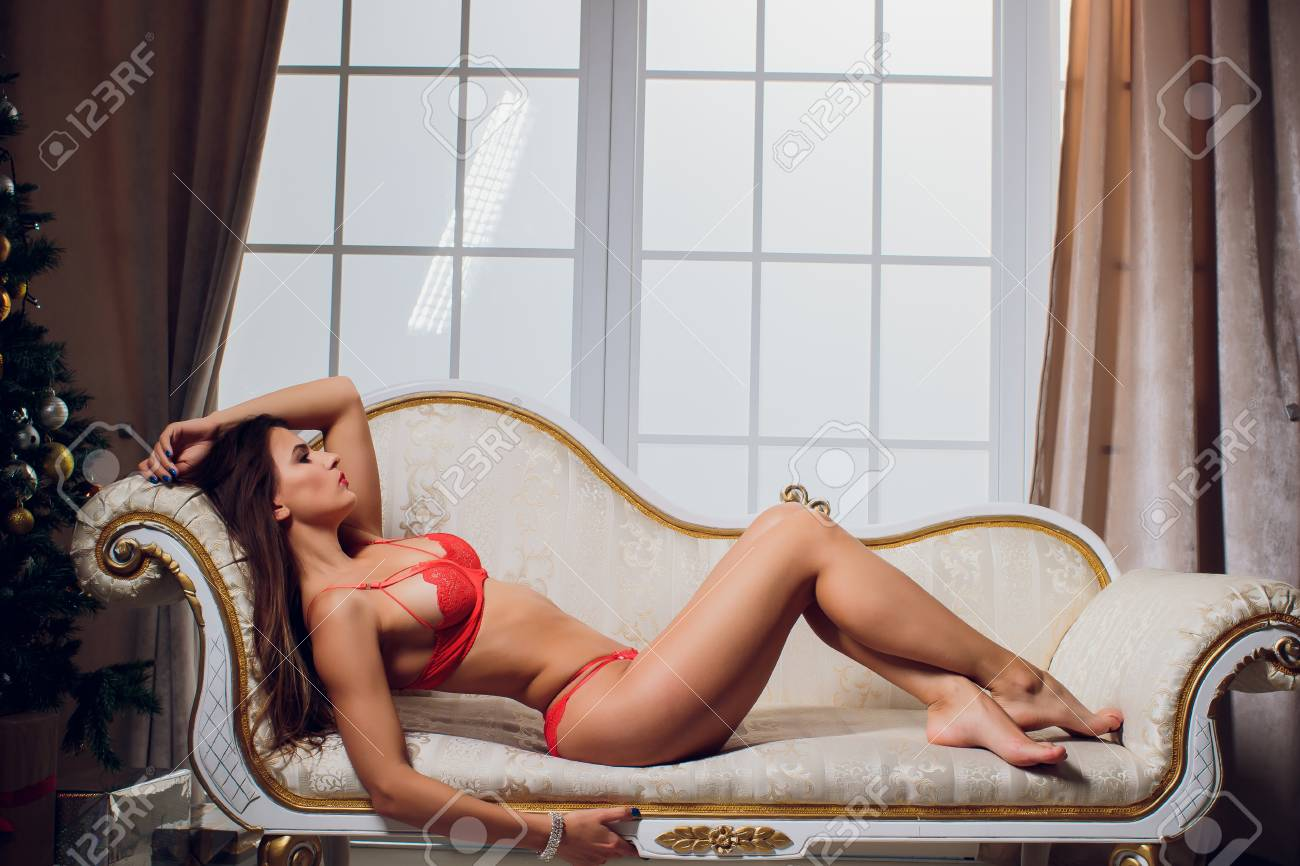 Beautiful brunette in red lingerie on a white couch. Stock Photo - 113480360