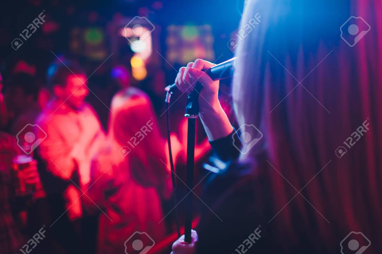 Entertianment at a wedding. A female singer is interacting with the crowd while a man plays an acoustic guitar. - 118565946