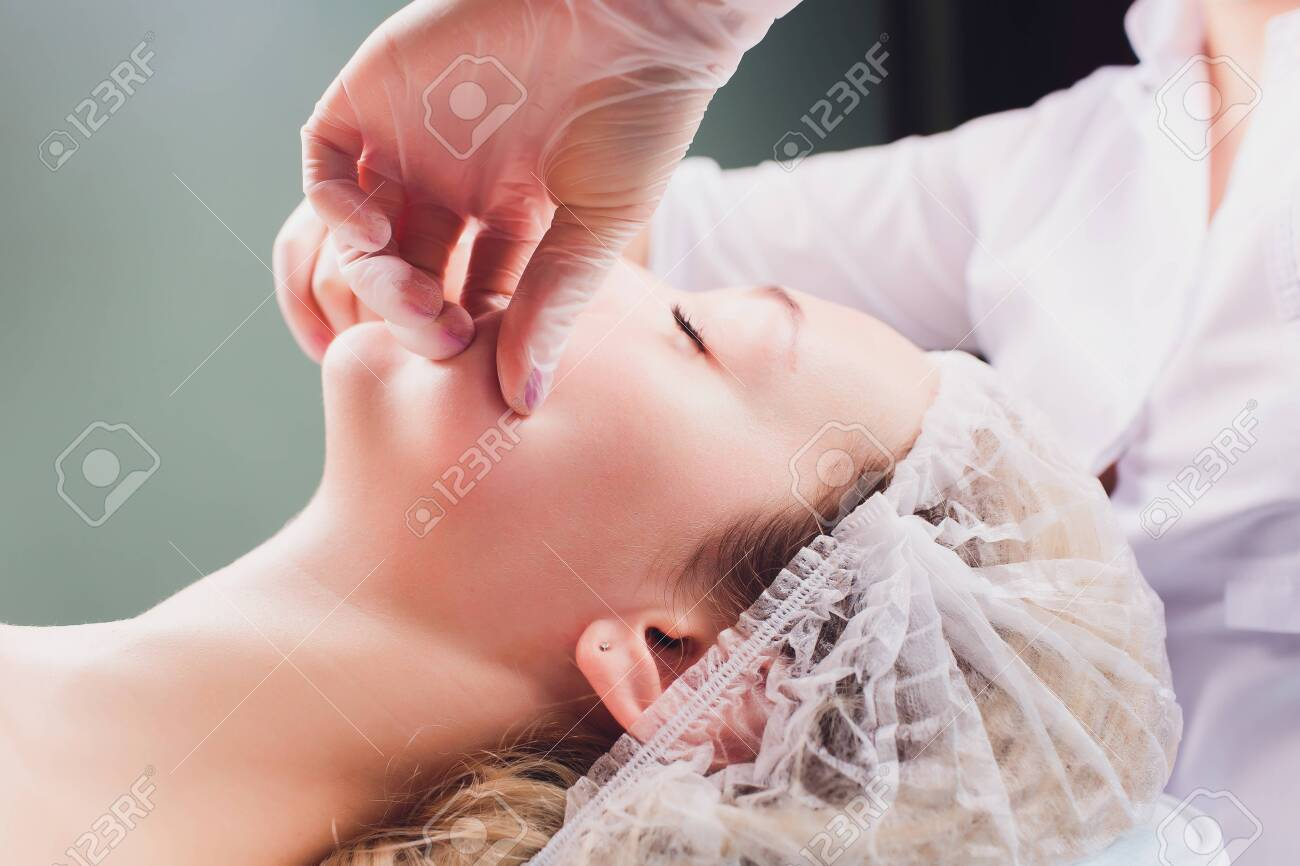 cosmetologist makes a buccal massage of the patients facial muscles. - 120897694